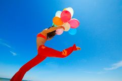 Girl with colorful balloons jumping Stock Images
