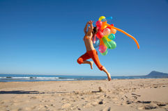 Girl with colorful balloons jumping on the beach. Girl with different colored balloons jumping on the beach stock photos