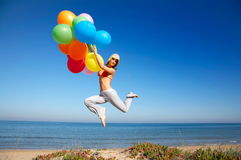 Girl with colorful balloons jumping on the beach. On a summer day Stock Photos