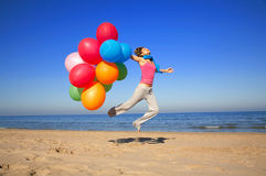 Girl with colorful balloons jumping on the beach. On a summer day royalty free stock image