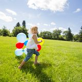 Girl With Colorful Balloons Running In Meadow Stock Photo
