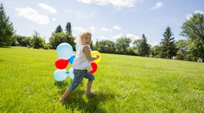 Girl With Colorful Balloons Running In Meadow Royalty Free Stock Photos