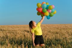 Girl with colorful balloons in sunset meadow. Happiness, enjoy the life, birthday party, bright moment, summertime, creativeness. Young girl with big bunch of royalty free stock photography