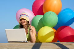 Girl with colorful balloons using a laptop. Happy girl with a bunch of colored balloons using a laptop royalty free stock image