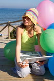 Girl with colorful balloons using a laptop. Girl with a bunch of colored balloons using a laptop on the beach stock photo