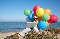 Girl with colorful balloons using a laptop. Girl with a bunch of colored balloons using a laptop on the beach Royalty Free Stock Images