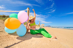 Girl with colorful balloons using laptop Royalty Free Stock Images