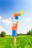 Girl with colorful balloons wears flower circlet. Looking girl with colorful balloons wearing flower circlet in summer Royalty Free Stock Images