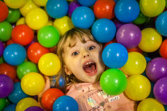 Girl among colorful balls Royalty Free Stock Image