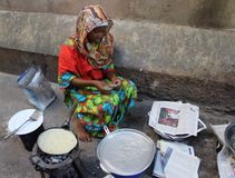 Girl in colorful clothes cooks in the streets of Stone town stock photo