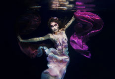 Girl in colorful clothes on the dark background underwater Royalty Free Stock Images