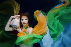 Girl in colorful clothes underwater Royalty Free Stock Photography