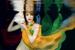 Girl in colorful clothes underwater Royalty Free Stock Images