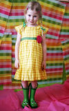 Girl in colorful dress and boots. Four year old girl in colorful gingham dress and green rubber boots Stock Images