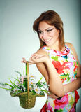 Girl in colorful dress with flowers basket Stock Images