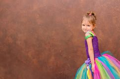 Girl in a colorful dress. Smiling on the background of a brown wall royalty free stock photography