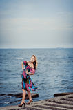 Girl in a colorful dress on the pier stock images