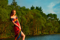 Girl in colorful dress at the sea. hippies at sunset enjoying a Stock Photography