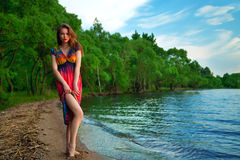 Girl in colorful dress at the sea. hippies at sunset enjoying a Royalty Free Stock Photography