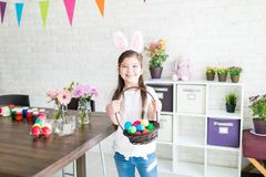 Girl With Colorful Easter Eggs Showing Contentment. Portrait of cheerful Caucasian girl showing Easter basket while standing at home royalty free stock image