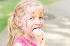 Girl with colorful face-painting eating ice cream Royalty Free Stock Photos
