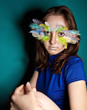 Girl with colorful feather on her face Royalty Free Stock Photos