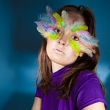 Girl with colorful feather on her face Royalty Free Stock Images