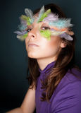 Girl with colorful feather on her face Royalty Free Stock Image