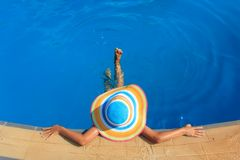 Girl with colorful hat in the pool Stock Photos