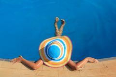 Girl with colorful hat in the pool Royalty Free Stock Images