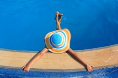 Girl with colorful hat in the pool Royalty Free Stock Image