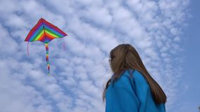 Girl with a colorful kite flying in the blue sky. With clouds stock footage