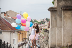 Girl with colorful latex balloons. Pretty girl with big colorful latex balloons posing in the street of an old town Stock Images