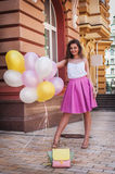 Girl with colorful latex balloons, urban scene, outdoors Stock Image