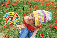Girl with colorful lollipop. Beautiful girl with colorful lollipop in a field with poppies stock photography