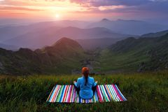 The girl on colorful mat is practicing Yoga. Beautiful mesmerising sunrise, orange sky with clouds, high mountains in fog. Summer. royalty free stock image