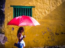 Girl with a colorful parasol. Walking by a yellow eroded wall in trinidad, cuba Stock Images