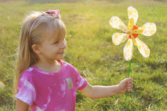 Girl with colorful pinwheel in sunset light Royalty Free Stock Photography
