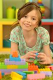 Girl with colorful plastic blocks Stock Photography