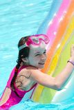 Girl on colorful pool float Royalty Free Stock Images