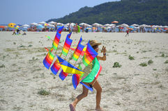Happy girl with colorful kite on beach Stock Photos