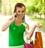 Girl with colorful shopping bags in the park Royalty Free Stock Images