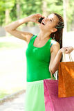 Girl with colorful shopping bags in the park Royalty Free Stock Photography