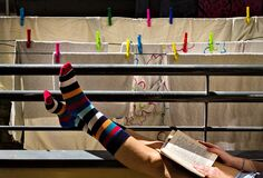 A girl in colorful striped socks is reading a book on the balcony in front of some clothes hanging out to dry Italy, Europe
