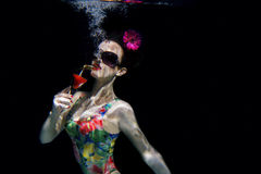 Girl in colorful stylish swimsuit with cocktail in her hand underwater Royalty Free Stock Photos