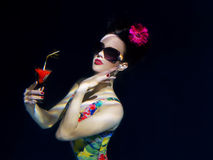 Girl in colorful stylish swimsuit with cocktail in her hand underwater Stock Photos