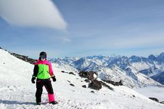 Girl in a colorful suit stands on top of a snowy mountain stock photography