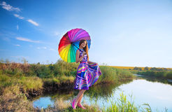 Girl with colorful umbrella at the riverbank stock photos