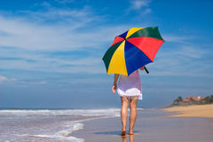 Girl with an colorful  umbrella on the sandy beach Royalty Free Stock Photo