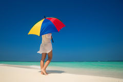 Girl with an colorful  umbrella on the sandy beach Stock Photo